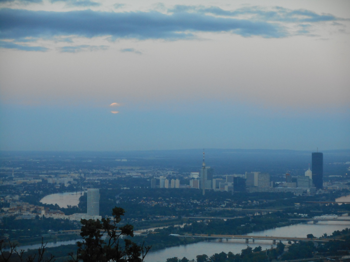 The moon appearing from behind the layer of clouds on the horizon.